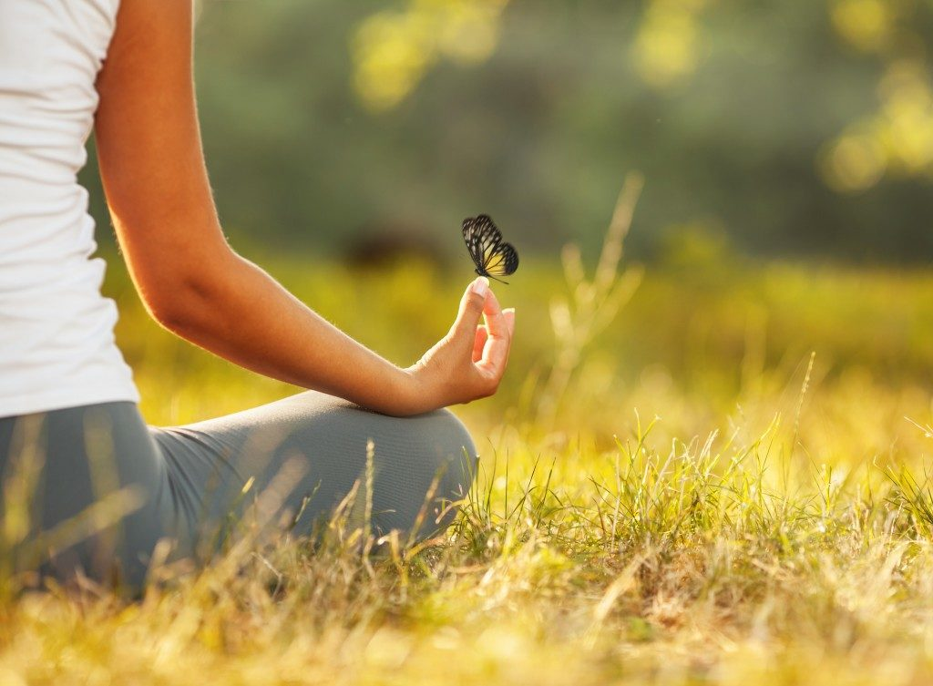 woman doing yoga with a butterfly on the top of her finger
