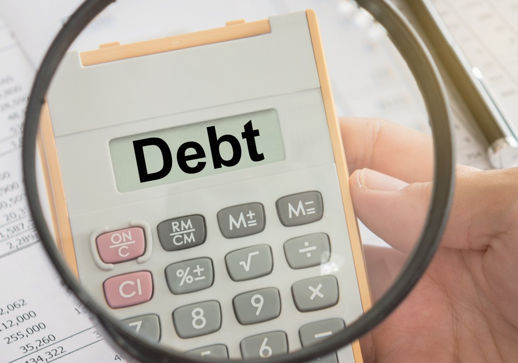 Debt concept text on calculator and magnifier