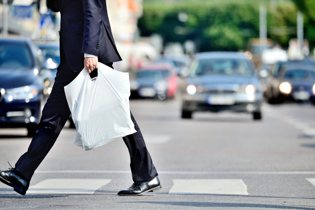 Man in suit with plastic bag crossing street