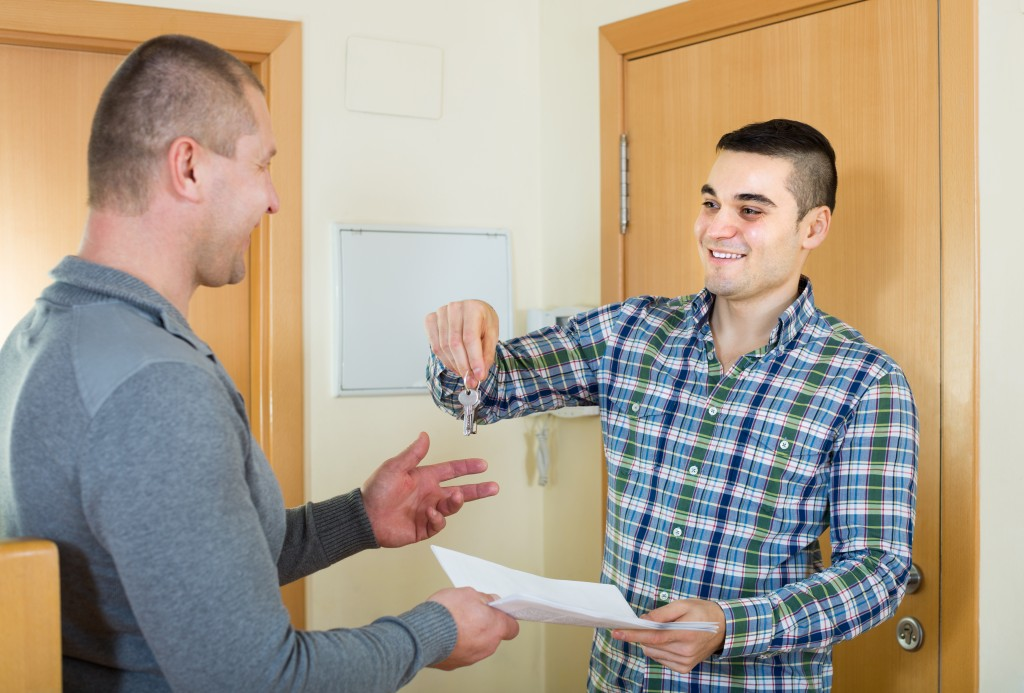 man handing over keys to landlord