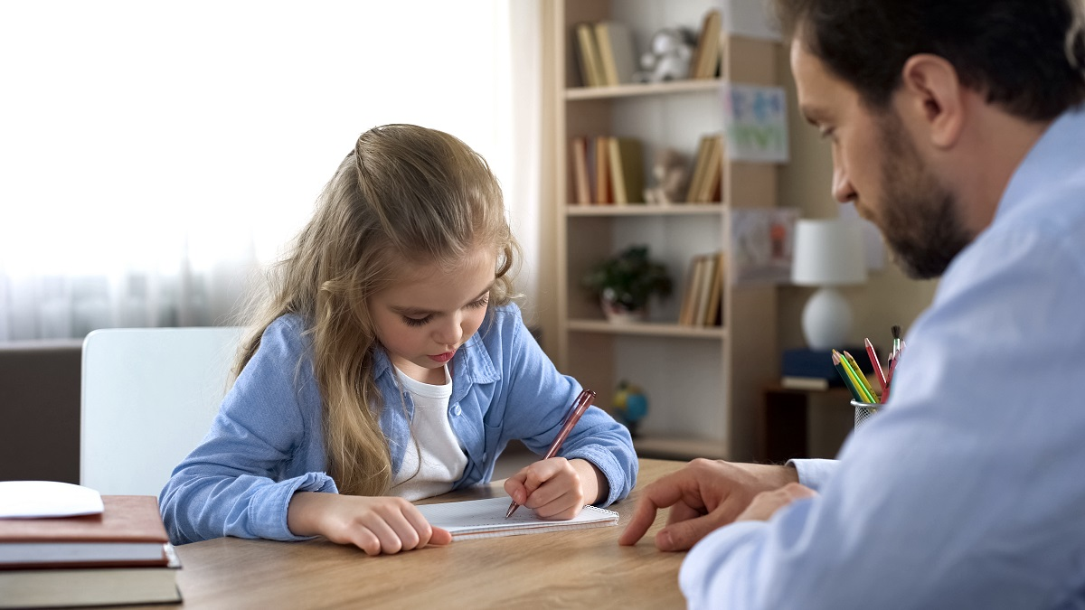 child writing with father