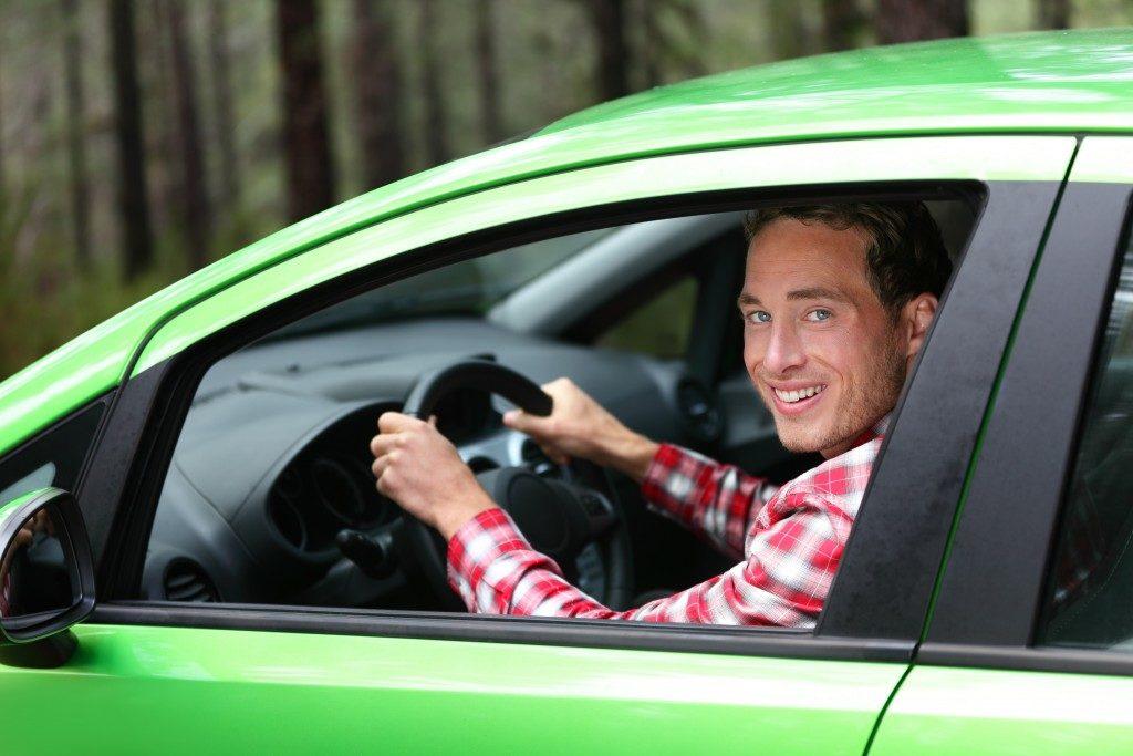Man driving a green car