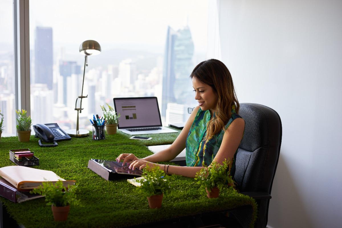 woman working on grass desk
